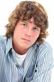 Attractive Sixteen Year Old Teen Boy in casual over white background.  Light brown curly hair and ha