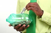 Close up of man putting a dollar in a piggy bank.  USD.