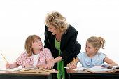 Teacher Helping Child in Classroom. Shot in studio over white.