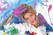 Beautiful young woman covered in paint. Shot in studio.