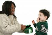 Beautiful African American woman sharing chocolate mints with two year old boy.