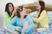 Three happy teen girls at slumber party doing hair and fingernails.