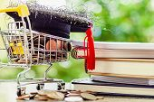 Square Academic Cap On Money Coin In Mini Shopping Cart Or Trolley And Stack Of Books Against Blurre poster