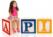 Attractive 3 year old mixed race american girl sitting on wooden block spelling API.