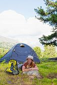 girl has a rest in green tent against mountains