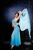 foto of dancing rain  - girl executes east dance in the rain against a dark background - JPG