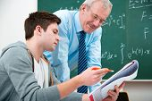 stock photo of tutor  - male student with a teacher in classroom - JPG