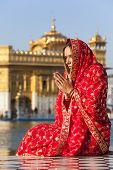 Woman in a red sari sat praying at Golden Temple.