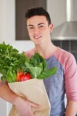 Good Looking Young Man Holding Bag Of Fresh Groceries
