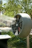 a water mister fan blows cool water into the air to cool down the area outside on a hot summer day