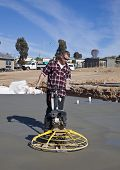 Workman smoothing newly poured concrete