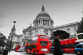 St Paul's Cathedral in London, the UK. Red buses in motion and man walking with umbrella.