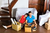 Real estate market - Young Indonesian couple moving in a home or apartment, they are sitting on the