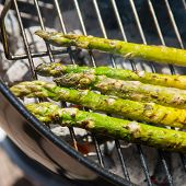 stock photo of charcoal  - Green asparagus on charcoal grill - JPG