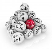 A pyramid of balls reading Play it Safe and one with the words Take a Risk to illustrate going beyon