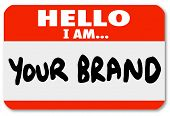 A red nametag sticker with words Hello I Am Your Brand to network yourself and promote your skills a