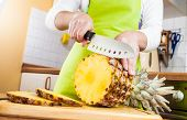 Mãos de mulher, corte o abacaxi fresco na cozinha