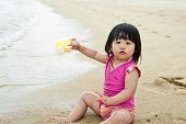 pic of curio  - Young toddler at the beach having fun and is curios - JPG