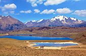 A great blue lake in a secluded valley in South America. The valley is located between the snow-capped mountains