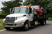 stock photo of towing  - White Flatbed truck towing an old red pickup truck - JPG