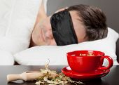 Man With Sleeping Mask Sleep On A Bed, Cup Of Herbal Tea In The Foreground. Focus On Tea Cup