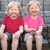 stock photo of identical twin girls  - Laughing cute identical blond twins sitting against a stone wall looking at the camera with charming smiles