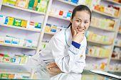 cheerful chinese pharmacist chemist woman standing in china pharmacy drugstore