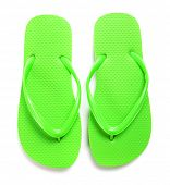 A pair of lime green flipflops on a white background