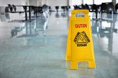 stock photo of janitor  - Caution yellow sign inside building hallway - JPG