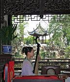 Young woman plays pipa in a garden in Suzhou, China