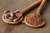 Cocoa powder and beans in spoons on wooden background