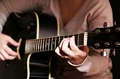 Acoustic guitar in female hands, close-up