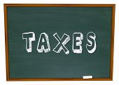 stock photo of year end sale  - Taxes Word Chalkboard Figuring Taxation Income Tax Return - JPG