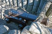 stock photo of cannon-ball  - Retro black metal gun in the fortification - JPG