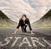 image of kneeling  - businesswoman on a road ready to run - JPG