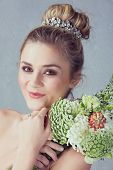 Portrait of a beautiful blond bride with a diamante headpiece. Hair in romantic top knot bun hairstyle. Wedding flowers.