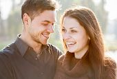 stock photo of she-male  - closeup of young couple outdoors laughing he looking at her she looking away - JPG