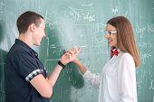 Two smiling highschool students standing on blackboard
