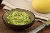 Guacamole In Bowl On Wooden Table