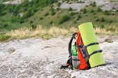 packed backpack at the peak of mountain