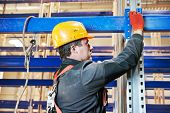 One warehouse worker in uniform during rack erection work installation