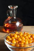 image of sea-buckthorn  - Sea buckthorn oil in a jug, sea buckthorn berries in a plate on a black background.