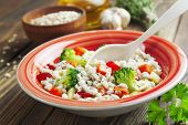 stock photo of porridge  - Barley porridge with vegetables in the plate on the table - JPG