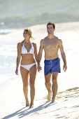 Young couple walking on paradisiacal beach