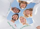 picture of huddle  - Low angle portrait of happy volunteers forming a huddle against blue sky - JPG