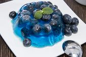 stock photo of jello  - Portion of Blueberry Jello with fresh fruits on wooden background - JPG