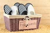stock photo of guest-house  - Slippers in basket on carpet on wooden background - JPG