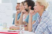 Group of smiling artists sitting in row during meeting at office