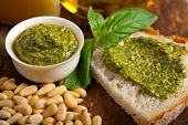 stock photo of pesto sauce  - Italian basil pesto bruschetta ingredients over old wood macro - JPG