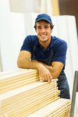 happy hardware store worker standing next to stacked wood